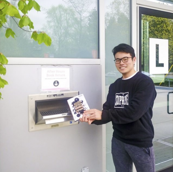 A Langara student returns a book using the Library's outdoor book drop.
